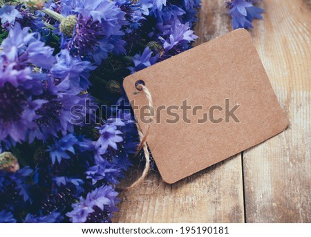 Rustic bouquet of blue cornflowers and brown cardboard tag on vintage wooden board
