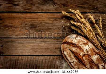 Rustic bread and wheat on an old vintage planked wood table. Dark moody background with free text space. Stock photo ©
