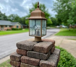 Rustic brick lamp post in quaint neighborhood on a cloudy day.