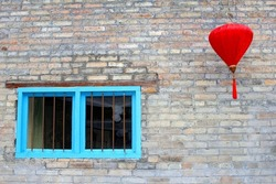 Rustic brick wall, blue windows and red Chinese lantern, symbolic for happiness, wealth and a long healthy life. Yangshuo, China