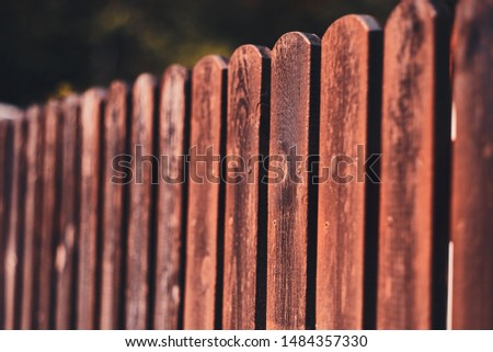 Rustic brown fence at bright sunny day with nobody on the photo.
