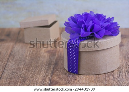 Rustic brown round gift box with a vivid purple flower and ribbon decorating it.
