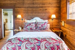 Rustic cabin bedroom with a large bed, quilt and wood-paneled walls and ceiling