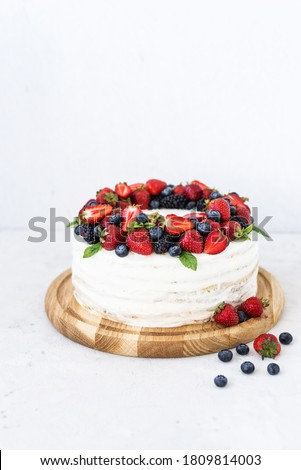 Rustic cake with fresh berries. Delicious fresh cake on a white background. Strawberry cake with blueberries and mint. Blueberry vanilla cream cake Foto stock ©