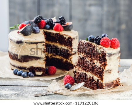 Rustic chocolate cake with buttercream frosting and decorated with berries and figs