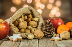 Rustic Christmas decoration, christmas sack with nuts, cookies, apples, oranges and pine cone decor.