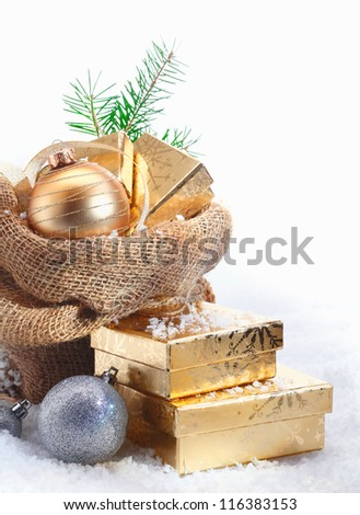 Rustic Christmas gift background with decorative baubles and golden gifts spilling out of a simple hessian sack onto the snowcovered ground with copyspace