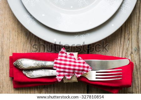Rustic christmas table setting with bright plates and silverware