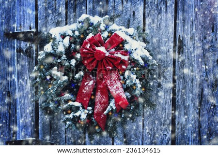Rustic Christmas wreath on old weathered door with Christmas lights in a snow storm.