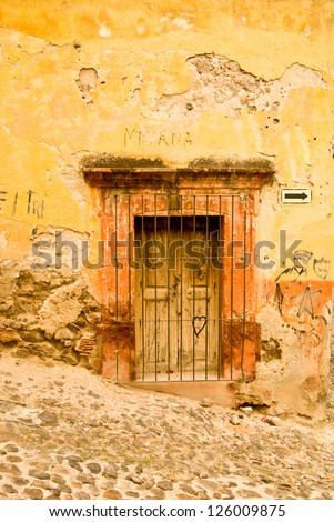 Rustic colonial building on a hillside street in old Mexico