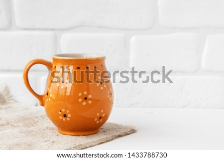 Rustic Cup on burlap on white brick wall background #1433788730
