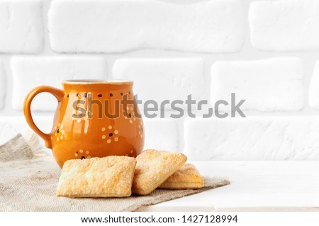 Rustic cup with cookies on white brick wall background