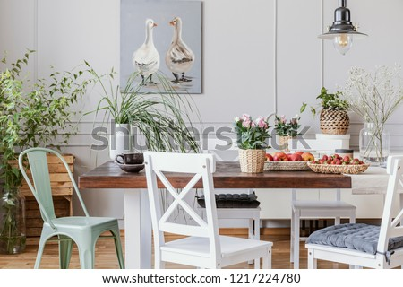 Rustic dining room with long table and white chairs and oil painting on the grey wall, real photo