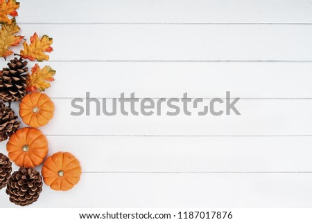 Rustic fall background of autumn leaves, pine cones and mini pumpkins with free copy space for text over a white rustic background. Image shot from overhead.