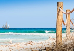 Rustic fence with wooden poles and rope on a deserted beach, in the background the rough sea. Wild beach in the island of Formentera Spain. Abstract ideal concept  to use as background out of focus
