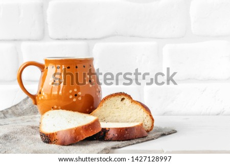 Rustic food. A cup with a drink, bread with poppy seeds on the kitchen table #1427128997