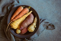 Rustic food ingredients, raw root vegetables such as organic Jerusalem artichokes, sweet potato, parsley roots and carrots, view from above