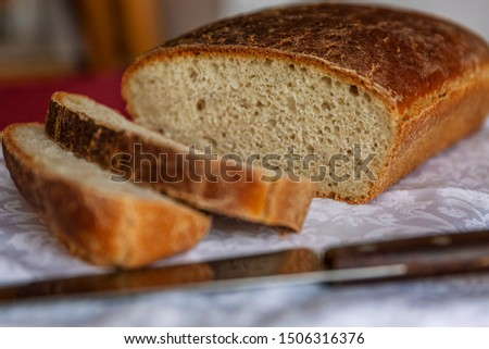 Rustic freshly baked bread with sliced slices on a wooden table. Close-up. #1506316376