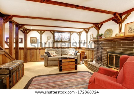 Rustic Furnished Family Room With A Stoned Background Fireplace, Old Couch, Country Style Rug And Ceiling Beams Design