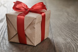 rustic gift box with red ribbon bow, on old wood table