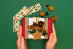 Rustic gift decoration hand made. Hands hold red present box covered with sackcloth, tissue paper, cinnamon sticks, fir branch, anise star, jute rope, craft cardstock tag. Present packaging tutorial.
