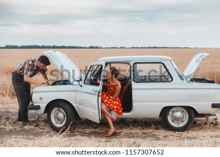 Rustic guy with a beautiful girl in the field next to the car