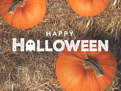 Rustic Happy Halloween Text With Ghost Icon Over Pumpkins and Hay From Directly Above