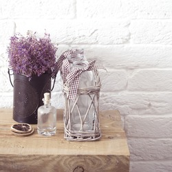 Rustic home decor, provence style. Lavender bouquet of dried field flowers and glass spice jars on wooden bench.