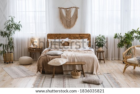 Rustic home design with ethnic decoration. Bed with pillows, wooden furniture, plants in pots, armchair and curtains on large windows in cozy bedroom interior, nobody, flat lay, panorama, free space