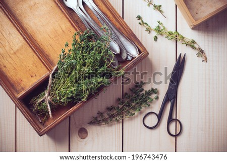 Rustic home kitchen still life, dried herbs, old boxes, antique cutlery and vintage scissors on a wooden table.