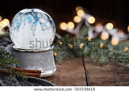 Rustic image of a Christmas snow globe surrounded by pine branches, cinnamon sticks and a warm gray scarf. Shallow depth of field with selective focus on snowglobe.