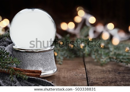 Rustic image of an empty Christmas snow globe surrounded by pine branches, cinnamon sticks and a warm gray scarf with copy space. Shallow depth of field with selective focus on snowglobe.