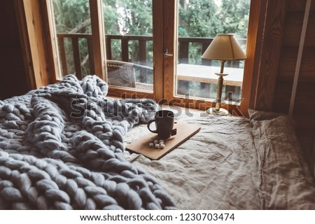 Rustic interior decoration of log cabin bedroom. Cozy warm blanket on bed by window.