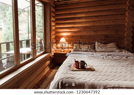 Rustic interior of log cabin bedroom. Cozy bed by big window. Breakfast on a tray in hotel.