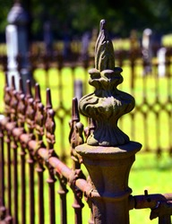 Rustic iron fence surrounds graves at a cemetery.  It is rusting but decorative and fancy.