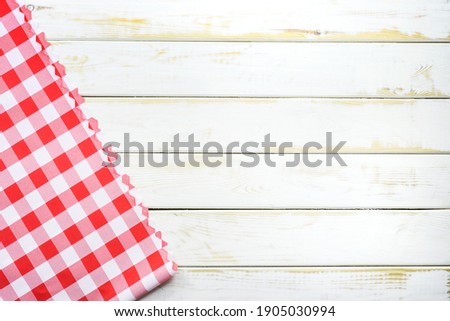 Rustic Italian cooking template - top view of vintage wooden table with a red checked tablecloth with copy space. Stock fotó ©