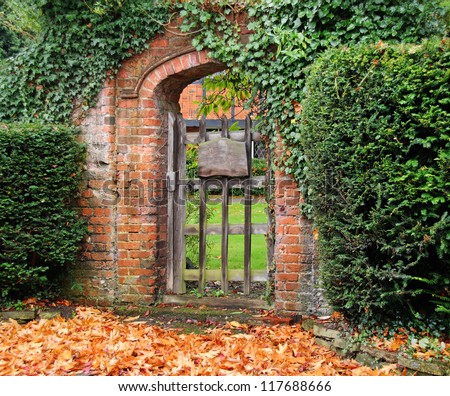 Rustic Ivy Covered Arched Gateway And Red Brick Wall Into