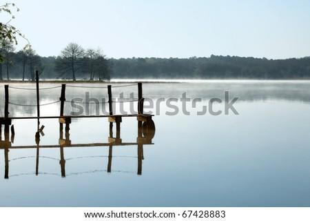 Rustic jetty on a zen-like idyllic lake in Aquitaine, France