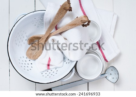 Rustic kitchen decor, enameled colander, wooden spoons and linen towels, dishes on a white board