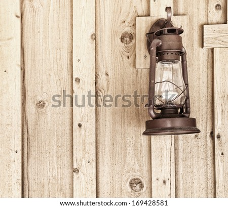 Rustic Lantern on Wood Panel Wall with room or space for text, copy, words.  Square with grunge, sepia treatment
