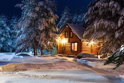Rustic log house, snow-covered pine trees, big snowdrifts, fabulous winter night. Rural beautiful winter landscape. Non-urban scene. New Year, Christmas. Copy space.