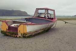 Rustic looking boat moored in Dunedin, Otago Peninsula at low tide