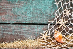Rustic marine background with copyspace on weathered turquoise blue wooden boards decorated with diamond mesh fish net, starfish and a seashell on a bed of beach sand, mementos from a summer vacation