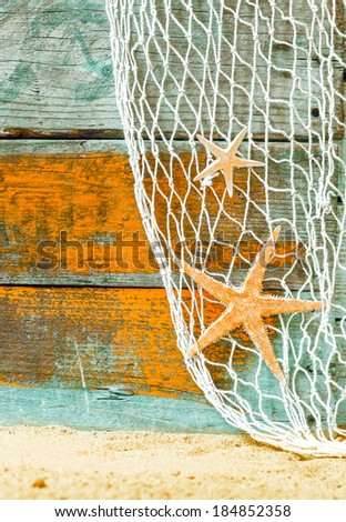 Rustic marine background with starfish suspended in a fishing net over weathered blue and orange painted wooden boards with copyspace and beach sand below