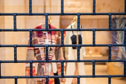 Rustic metal lattice background. Locked up / locked down / shut down / closed concept. Quarantine. Closed and shuttered entrance to department store during COVID-19