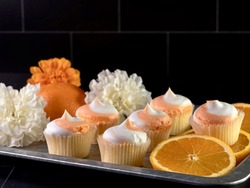 Rustic metal tray filled with fresh orange slices, mini orange creamsicle cupcakes with white and orange frosting and artificial flowers on a black subway tile background.