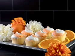 Rustic metal tray filled with mini orange creamsicle cupcakes decorated with white and orange frosting, garnished with fresh orange slices along with white and orange flowers.
