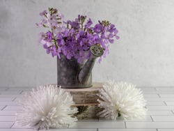 Rustic metal watering can filled with fresh purple wildflowers, dame's rocket, sitting on top of two pieces of real wood with 2 artificial white flowers on a white subway tile counter plaster.