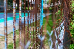 Rustic net fence and gate concept photo. Metallic net with brown rust. Old garden fence. Metallic wire fence in rust. Summer sport yard behind net fence. Empty tennis court in abandoned hotel