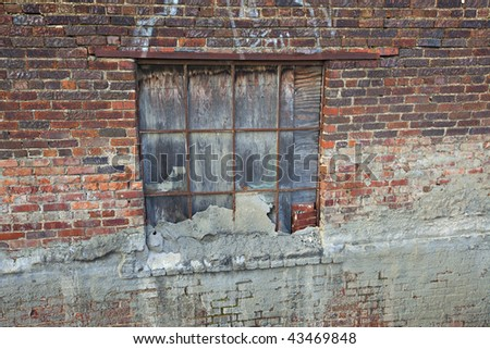 Rustic old brick wall with window that has been boarded up